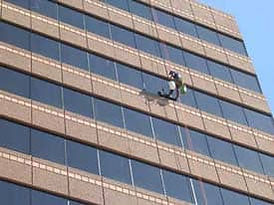Closeup of Worker on swing at US Bank building cleaning & restoring the curtainwall