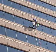 Closeup of Worker on swings at US Bank building cleaning & restoring the curtainwall.