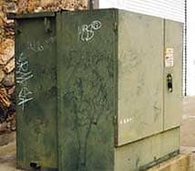 Faded & oxidized green utility box with grafitti that is an eyesore.
