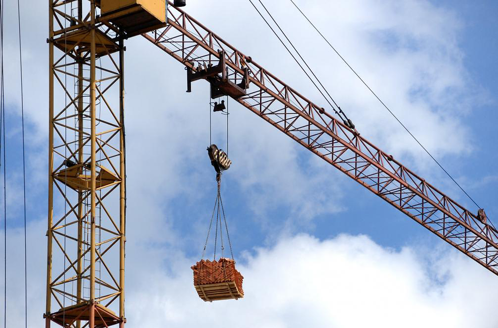 A tower crane with the hoist carrying the load.