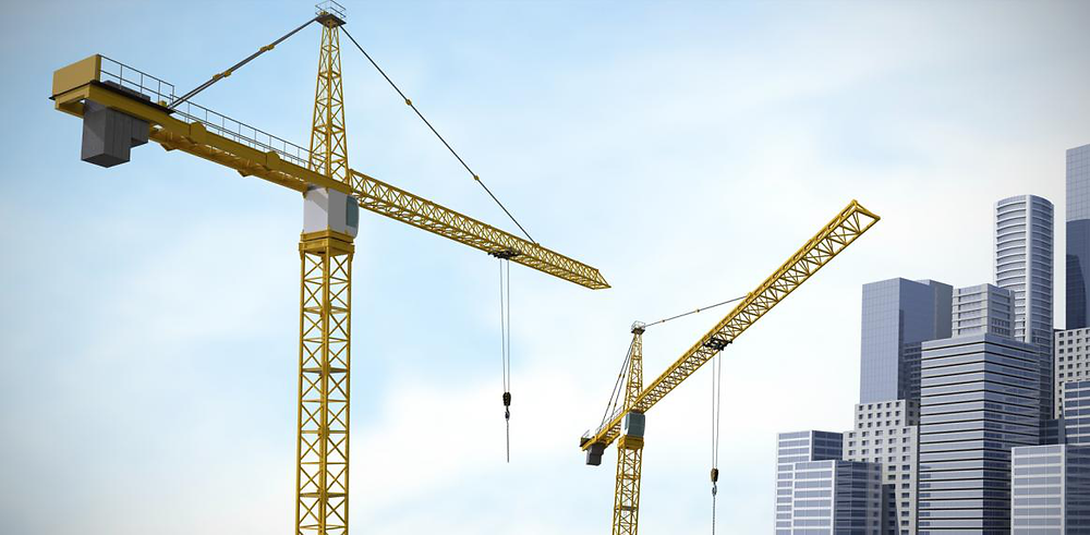 Two construction cranes with tall buildings and blue sky in the background