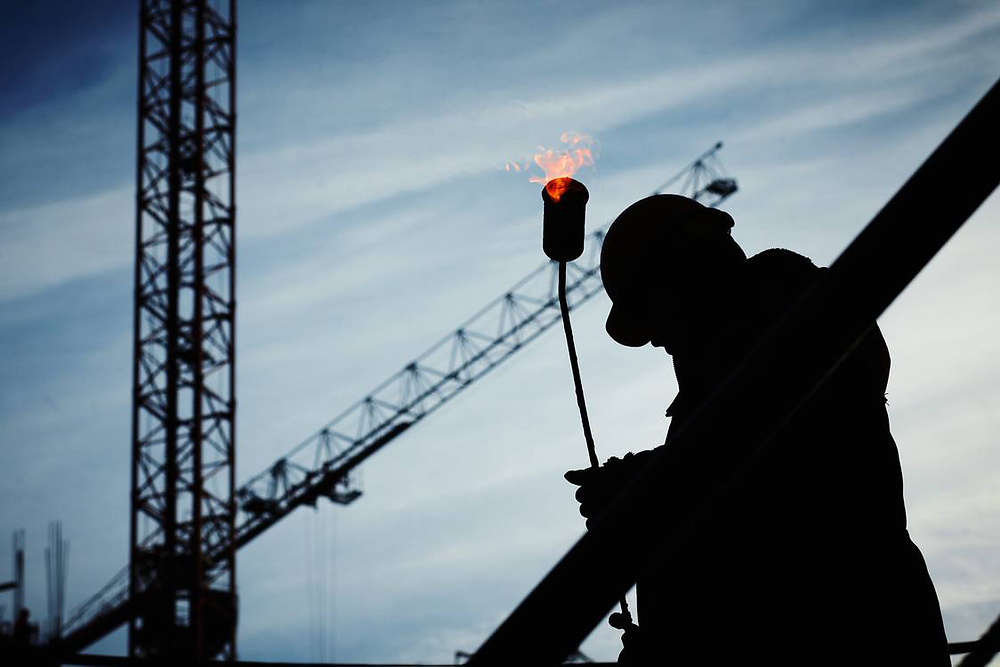 Construction worker against a crane in the background.