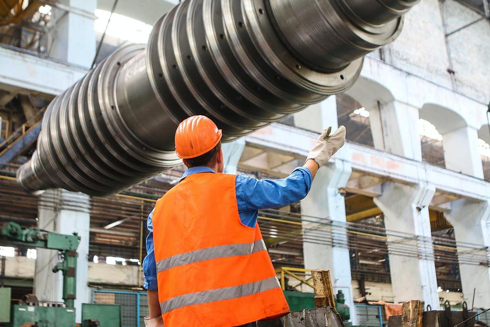 A construction worker standing near gray metal equipment.