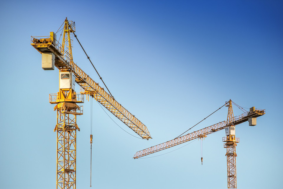 Two industrial cranes being used in construction.