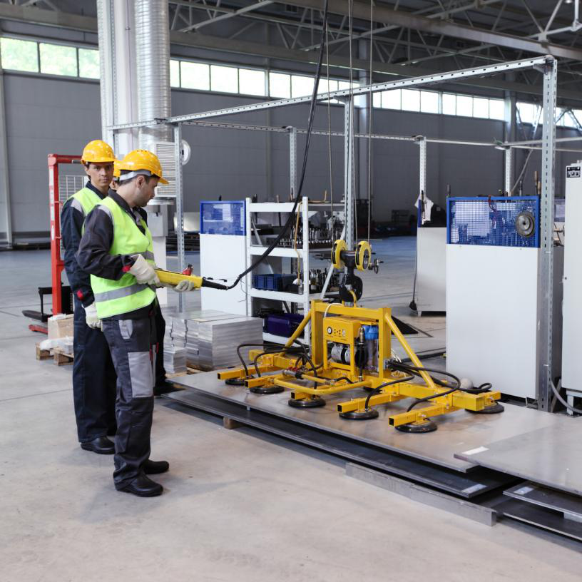 Workers operating a magnet lifting device.