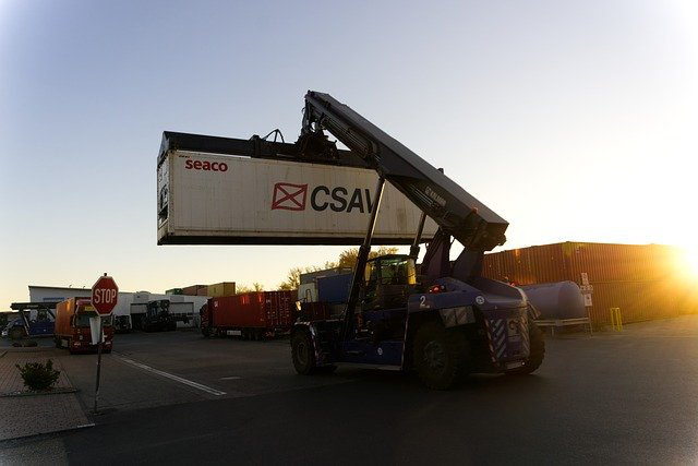 A mobile crane carrying a heavy container.