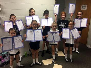 Goggin-Carroll Irish dancers proudly displaying Grade Exam certificates