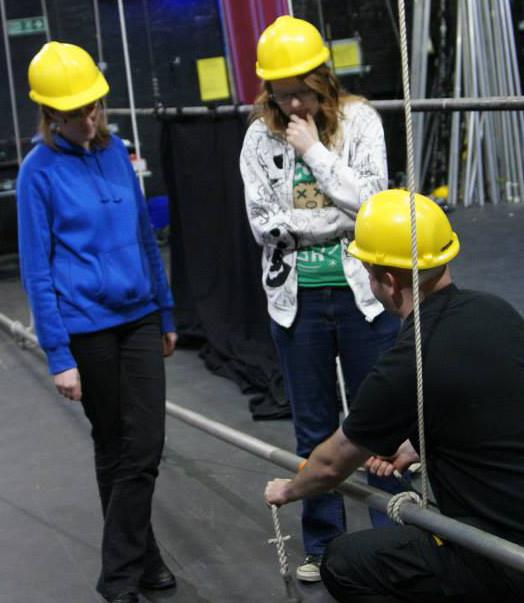 Three technicians from The Penguin Club in hard hats examining a lighting bar