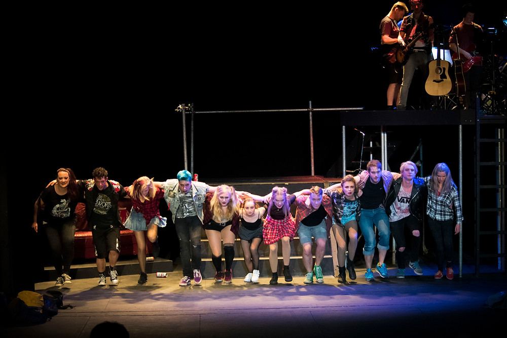 The cast of Green Day's American Idiot in a choral line, dressed in neopunk costume and stomping the stage.