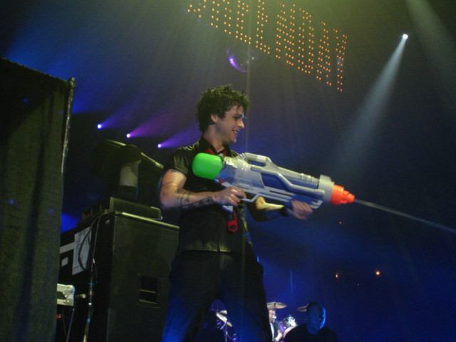 Billie Joe Armstrong with a water pistol on stage.