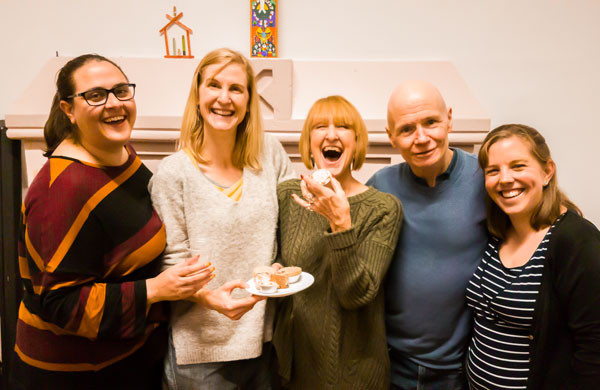 Five members from recent Pied Pipers committees smiling and laughing with mince pies