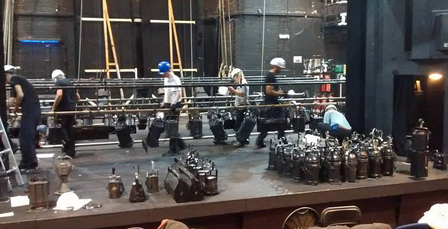Theatre technicians rigging lights to a lighting bar