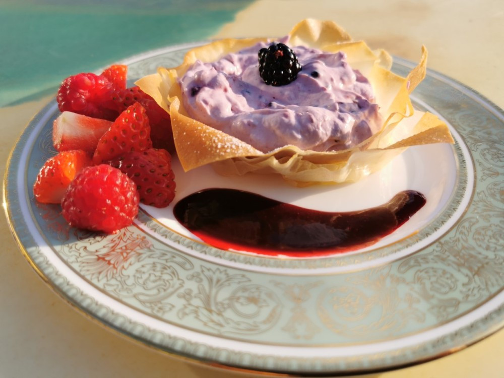 Berry filo tartlet served with fresh berries and a blackberry coulis