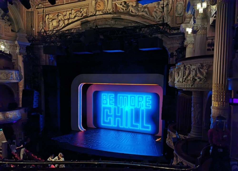 The Stage of Be More Chill with the title in neon lettering