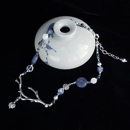 blue carved sodalite, silver flowers and crystal beads hang a polished silver branch and flower necklace