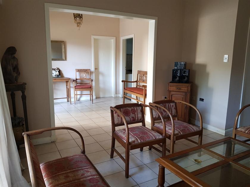 Living vista hacia la entrada - puerta hacia la cocina y puerta garage