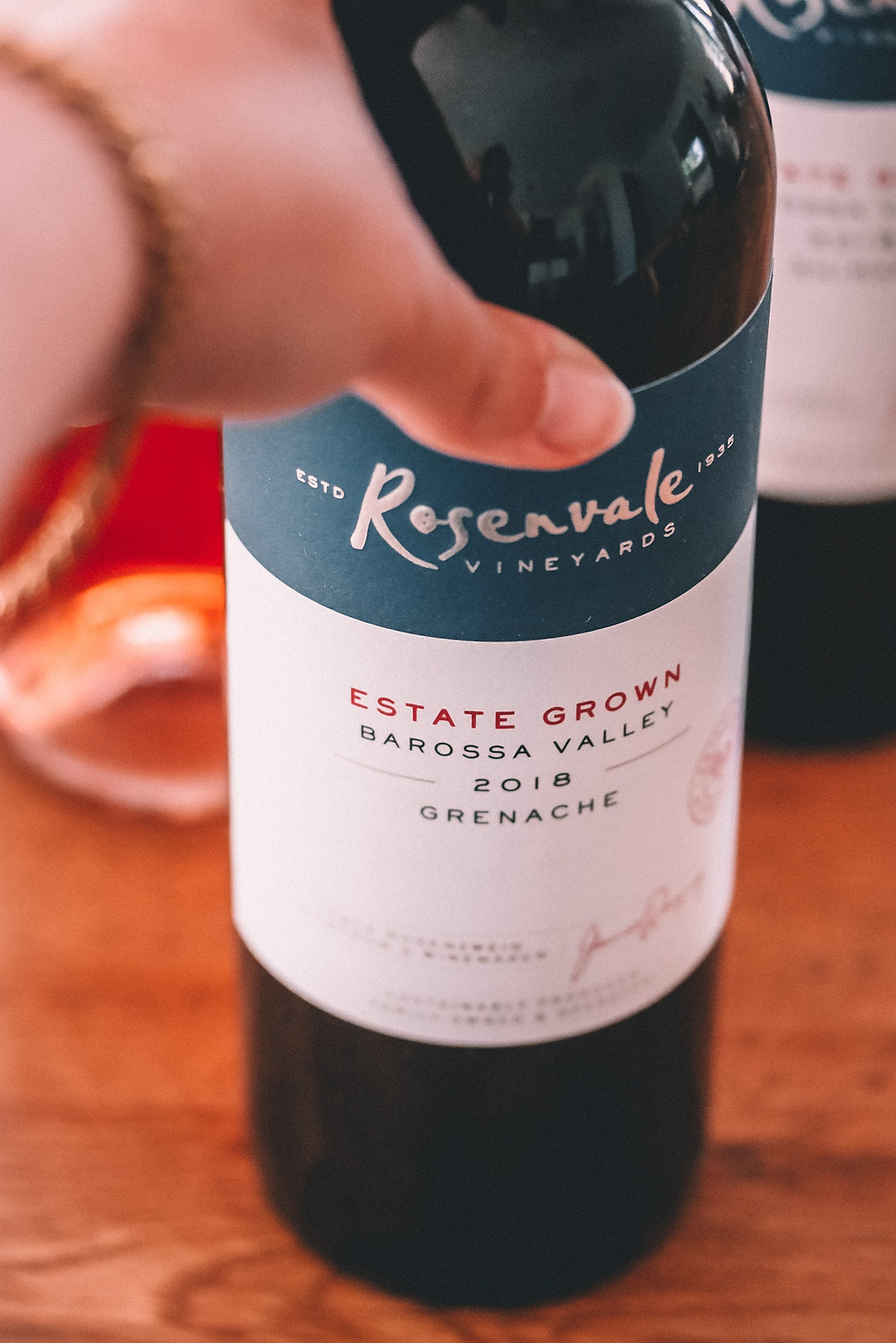 Hand reaching for a bottle of grenache red wine