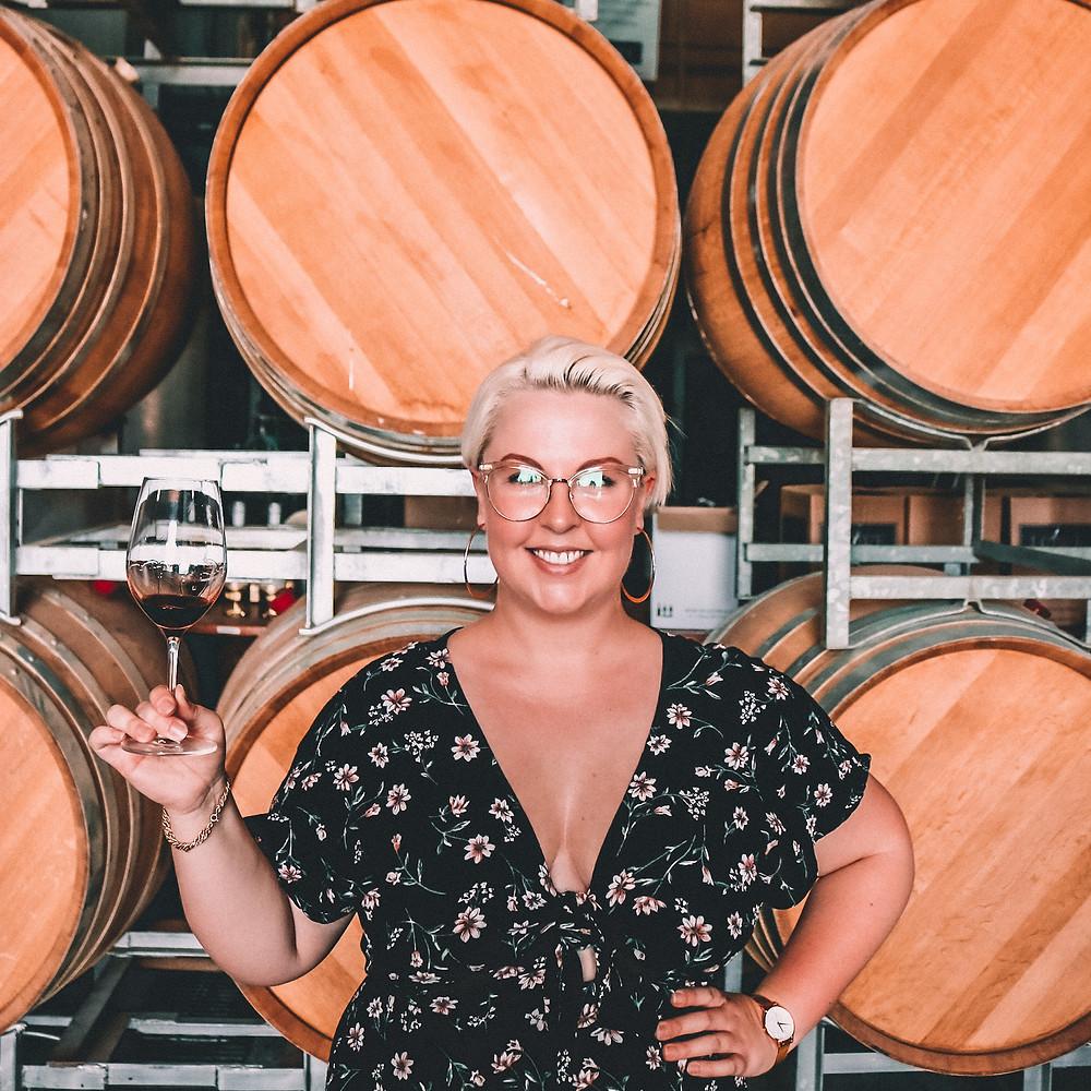 Woman standing in front of wine barrels