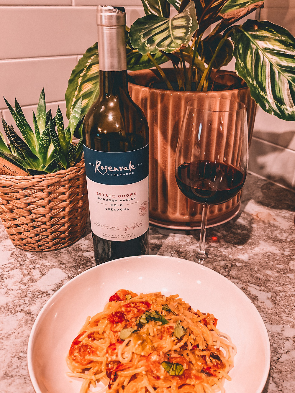 Bottle of red wine with pasta dish