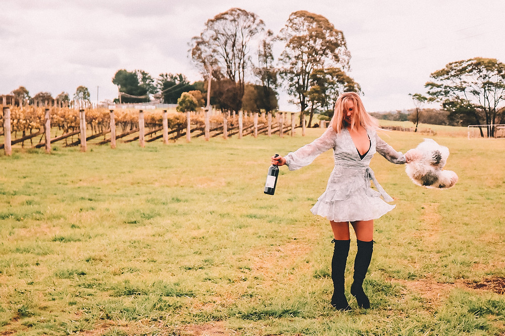 Girl at a winery spinning in the vines