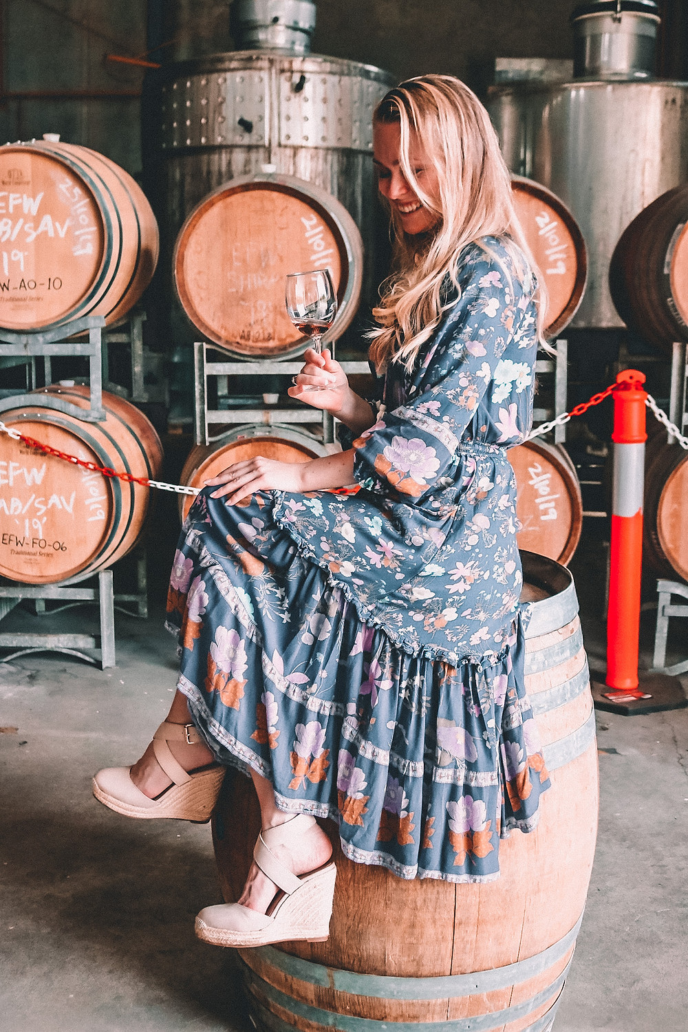 Girl sitting on a barrel drinking rosé at a winery