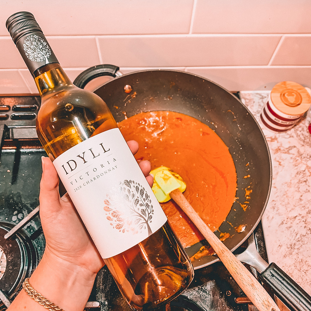 Bottle of wine with curry on stove