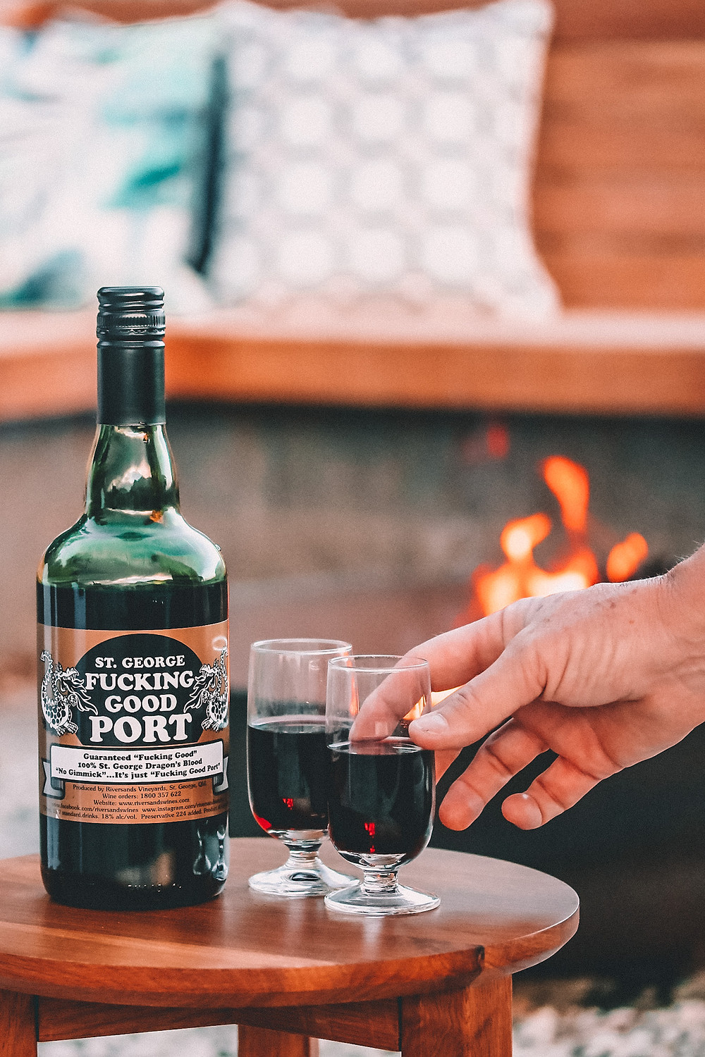 A bottle of port and two glasses by the fire