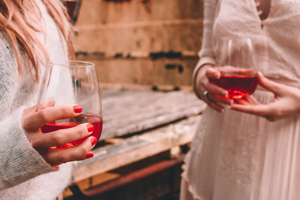 Two girls at a winery drinking rosé
