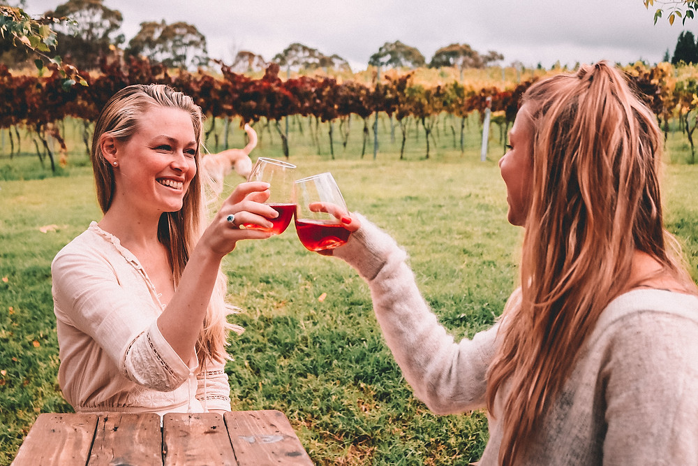 Two girls drinking rosé at a winery, wine tasting