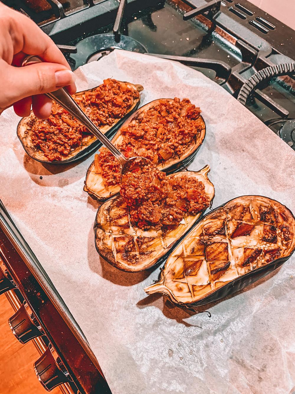 Spooning mince onto roasted eggplants