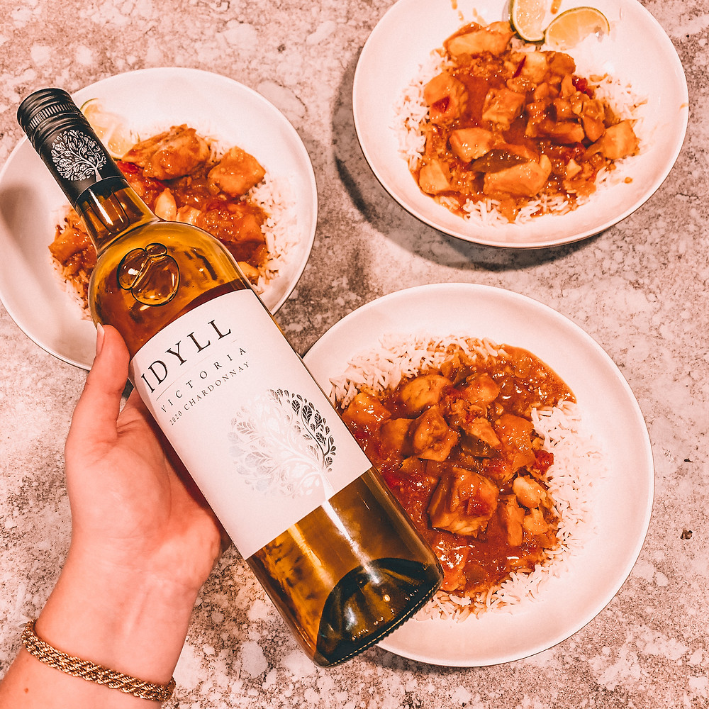 Bottle of wine with curry & rice in bowls