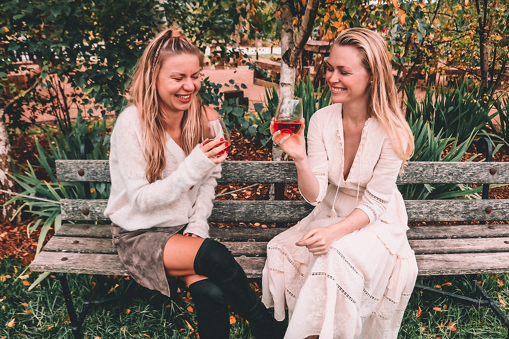 Two girls drinking rosé at a winery
