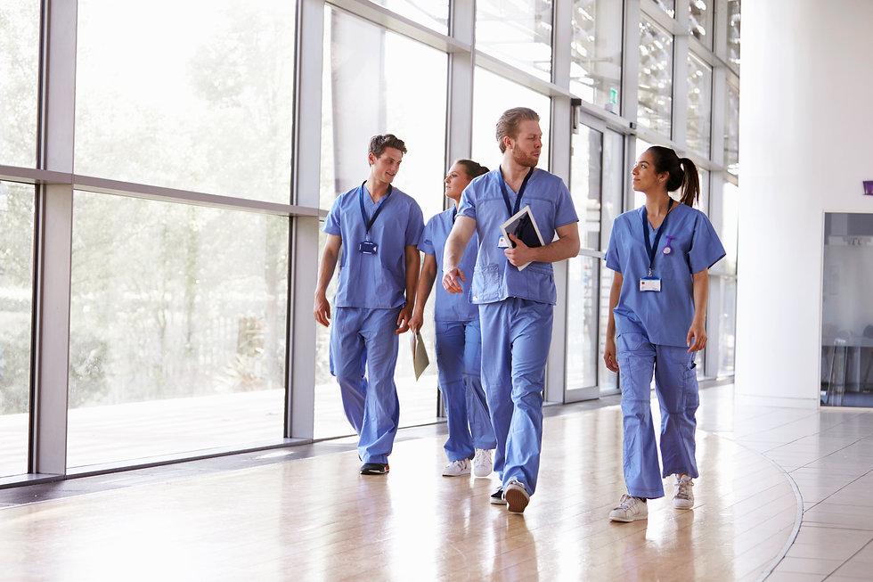 Four healthcare workers in scrubs walkin