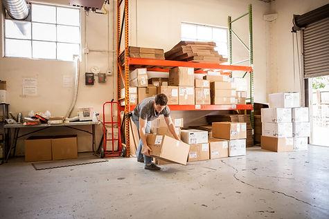 Worker Lifting Cardboard Box