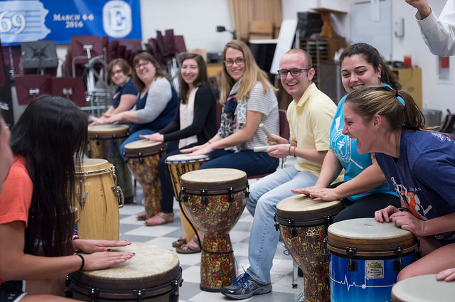 Students laughing and playing drums