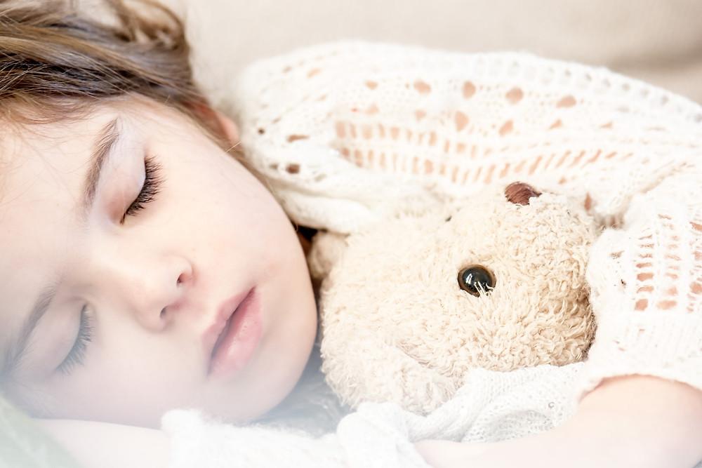 Little girl sleeping holding a teddy bear
