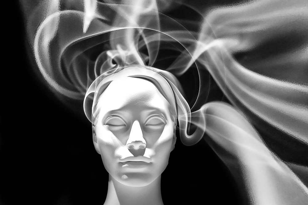 white face sculpture on black background, eyes closed, smoking coming out of head
