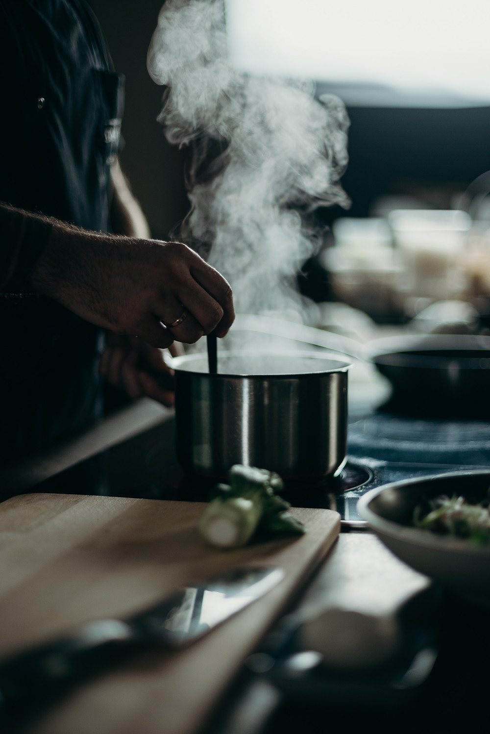 person stirring a steaming pot on a stove, a knife on a cutting board in the foreground
