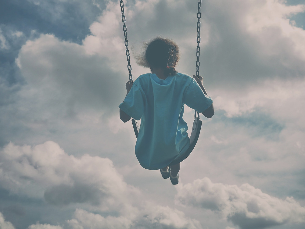girl swinging, clouds and sky in background