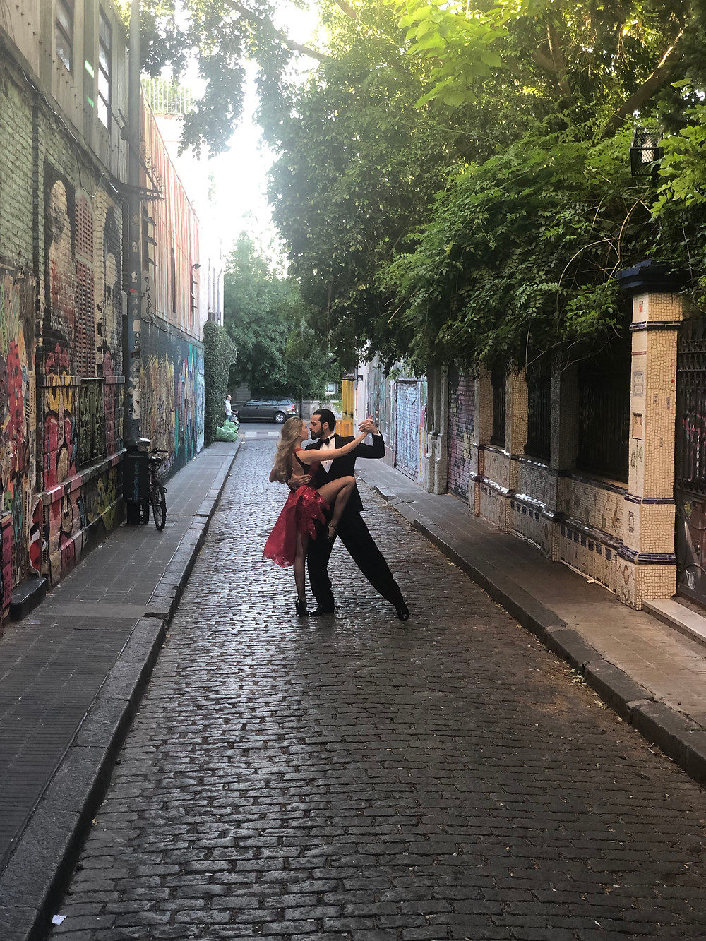 Man and woman dancing in a narrow city street