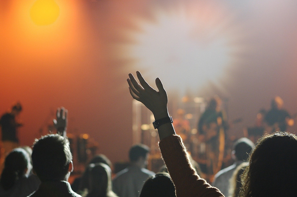 audience at a music concert, some with hands raised in the air
