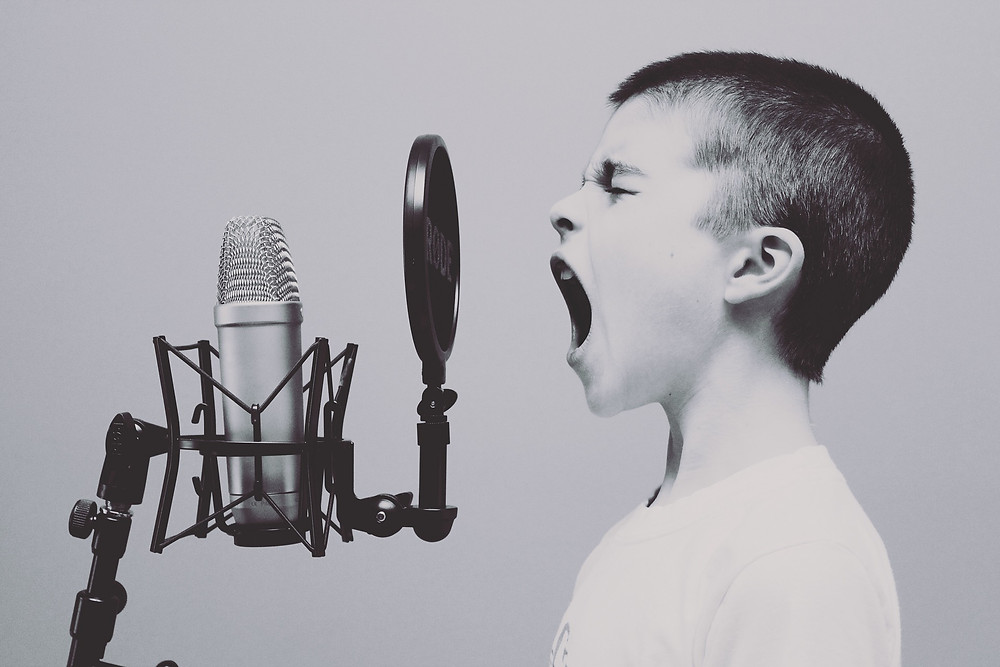 boy singing into a recording microphone