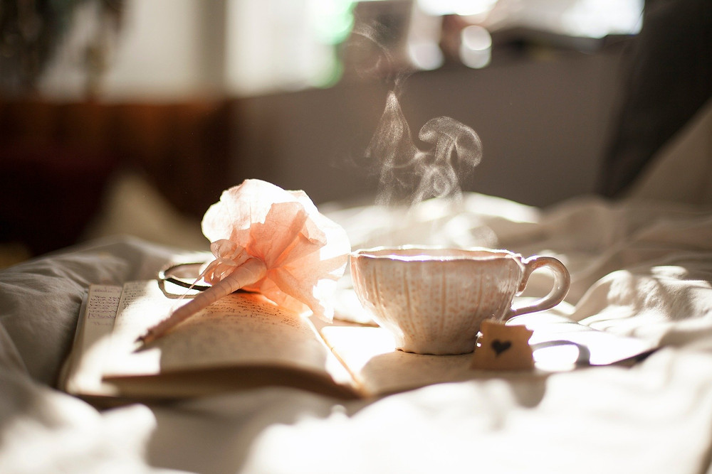 open journal with pen, covered with ribbon, and a cup of tea sitting on top, steam going up from the tea