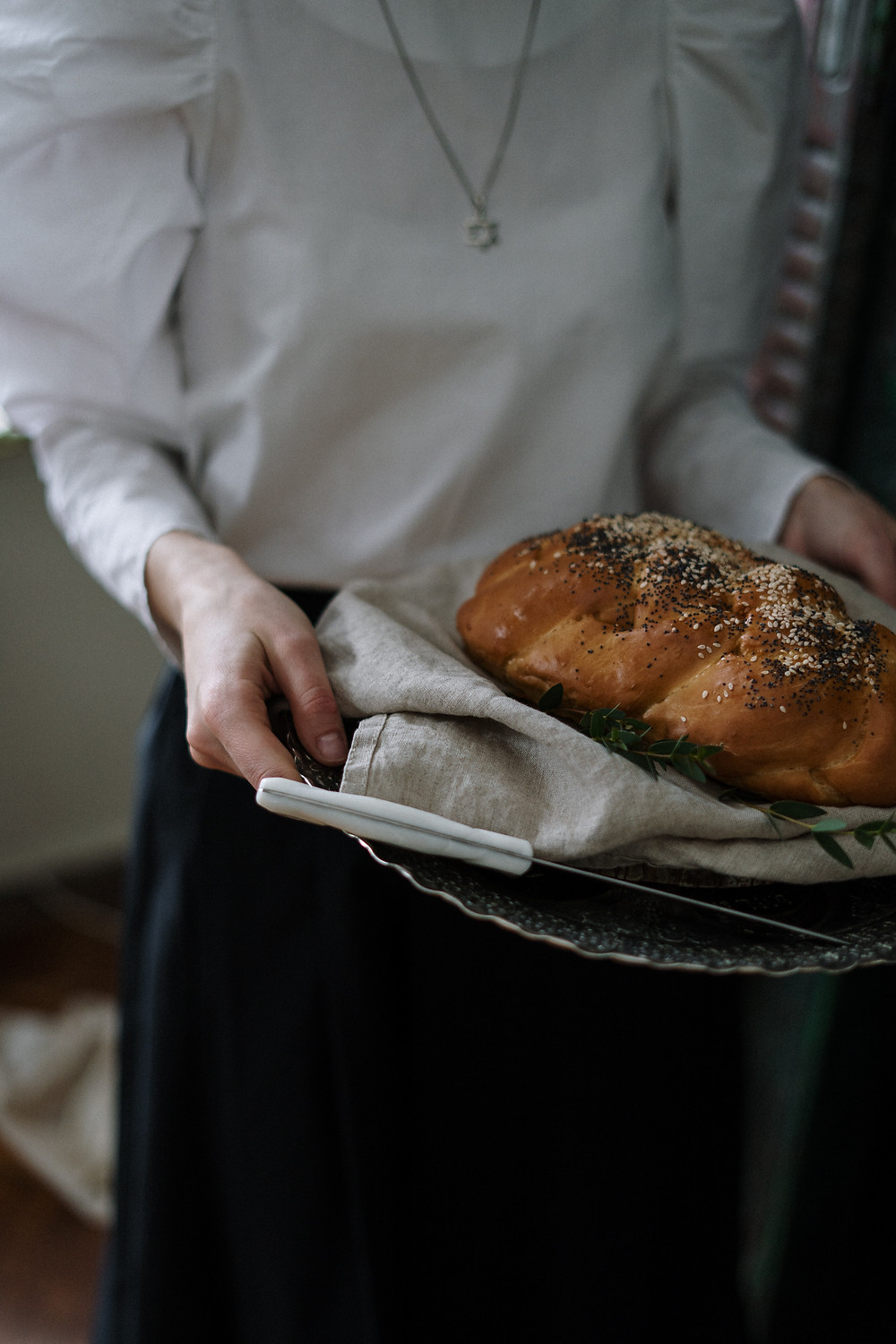 A woman carrying a platter with challah bread and knife on it, free image courtesy of Pexels