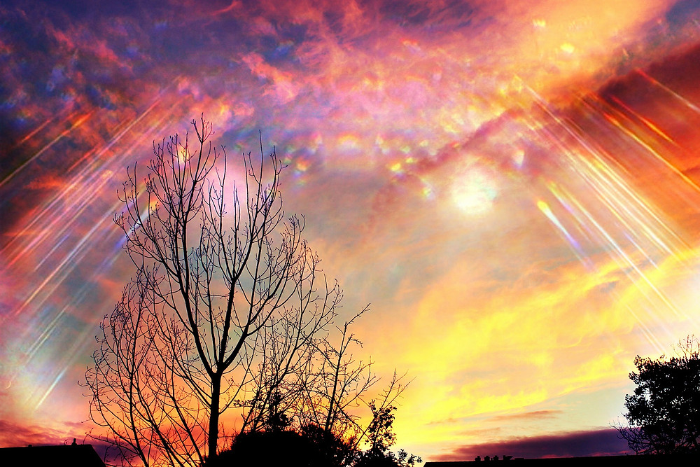 colorful clouds at sunset with rays from sun streaking through the clouds
