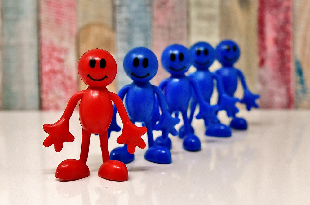 plastic figurines in a row, all with smiles, the one in front is red, the others are blue