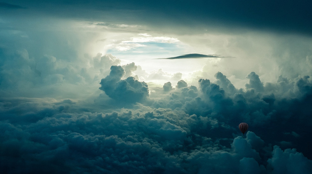 cloud-filled sky with one clear opening in the center, a small hot air balloon drifting among the clouds