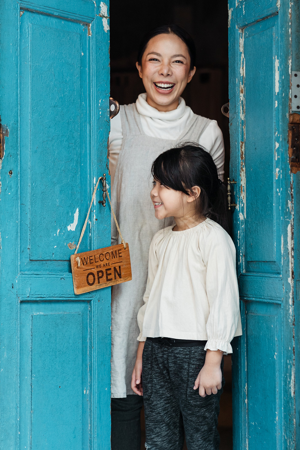 woman and little girl standing in open doorway with a welcome sign on the doorknob