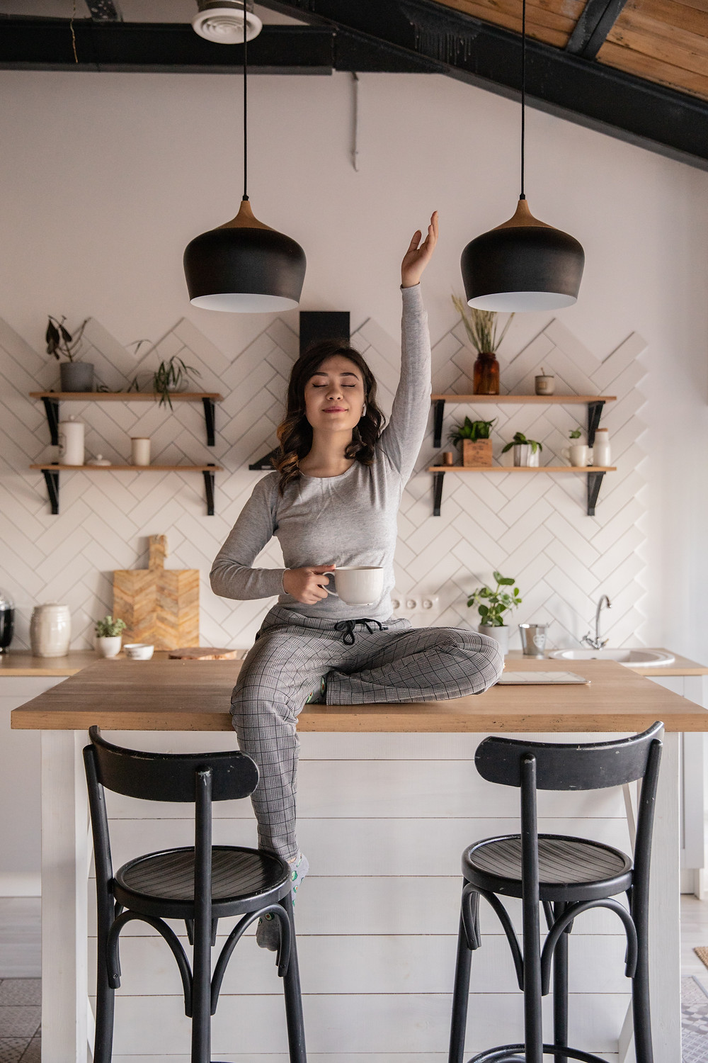 Woman sitting on kitchen table, coffee mug in one hand, other hand is raised to the ceiling, her eyes are closed. Free image courtesy of Pexels
