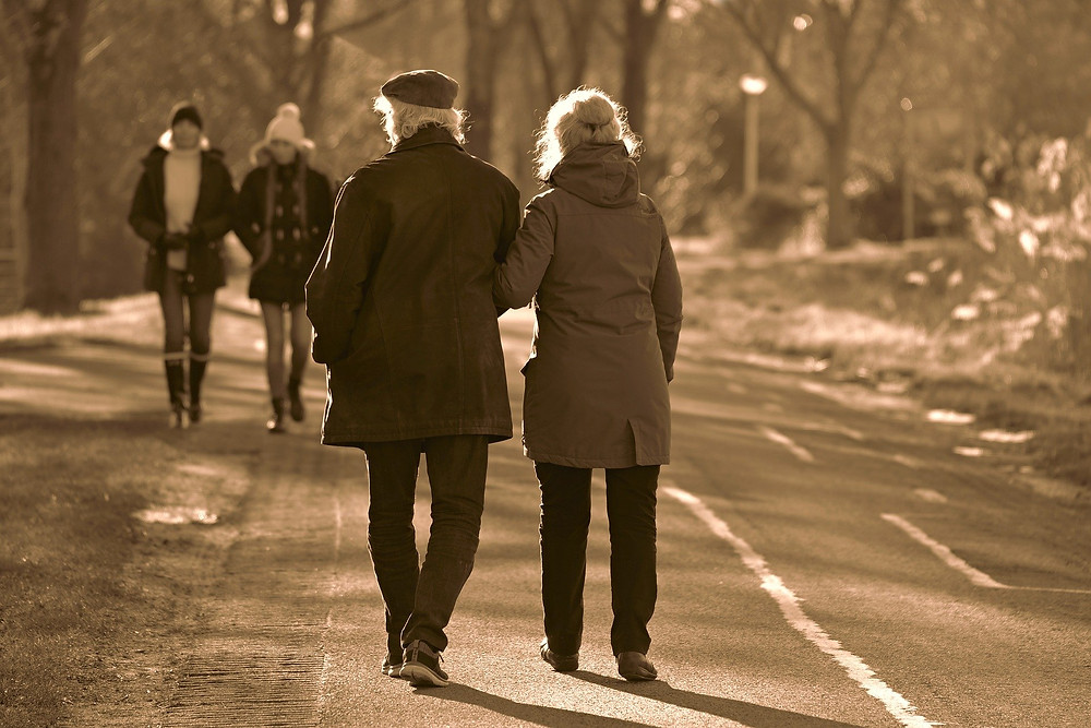 older man and woman walking arm in arm wearing coats